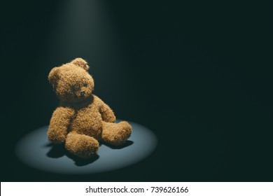 Teddy bear with torn eye illuminated by spotlight sits in dark room. Child abuse and violence concept.