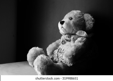 Teddy Bear toy alone on wooden floor vintage style.Black and White