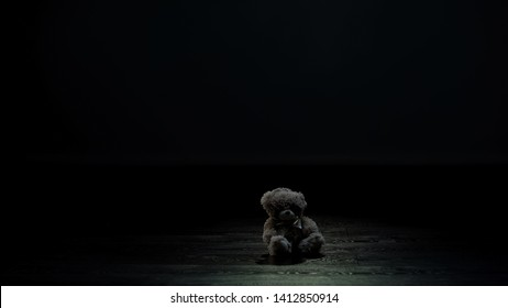 Teddy bear toy in dark room, loneliness and lost childhood concept, sadness