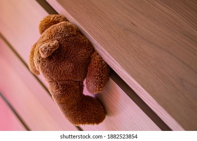 teddy bear toy, with its head clamped in a box, as a concept of child abuse