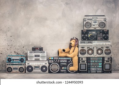 Teddy Bear toy with leather aviator's hat and goggles sitting on retro old school design ghetto blaster boombox stereo radio cassette tape recorders tower from circa 80s. Vintage style filtered photo