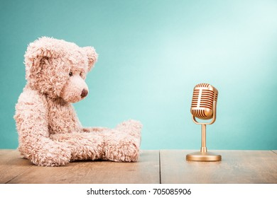 Teddy Bear toy with retro golden microphone front gradient mint green wall background. Vintage old instagram style filtered photo