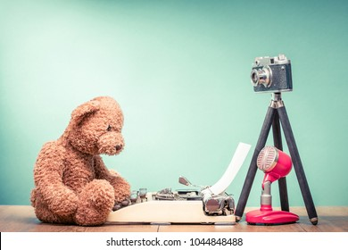 Teddy Bear toy sitting on old wooden desk with retro typewriter, outdated film photo camera on tripod and microphone front mint green wall background. Blogging concept. Vintage style filtered photo