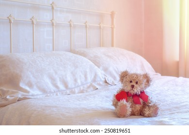Teddy bear toy sitting on the bed holding a red heart