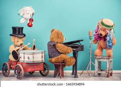 Teddy Bear toys music band: vocalist with colored hair, retro old microphone, bear in cylinder hat playing drum, flying angel with fiddle, grand piano player. Vintage nostalgia style filtered photo