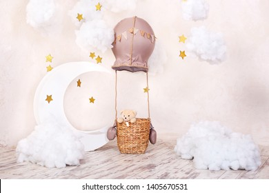 Teddy bear traveler and pilot. Childhood dreams. Stylish vintage children's room with aerostat, balloons and textile clouds. Children's location for a photo shoot: aerostat, balloon and clouds.