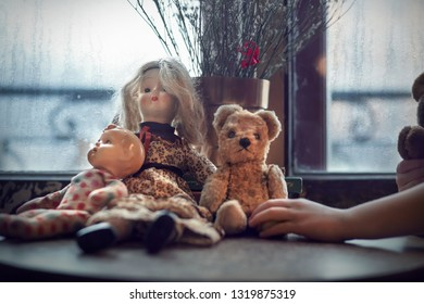 Teddy bear and two dolls on the table in front to window. Image with selective focus and toning