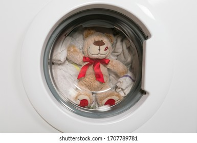 Teddy bear washes in the washing machine.
