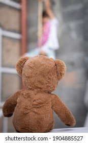 Teddy bear watching girl playing