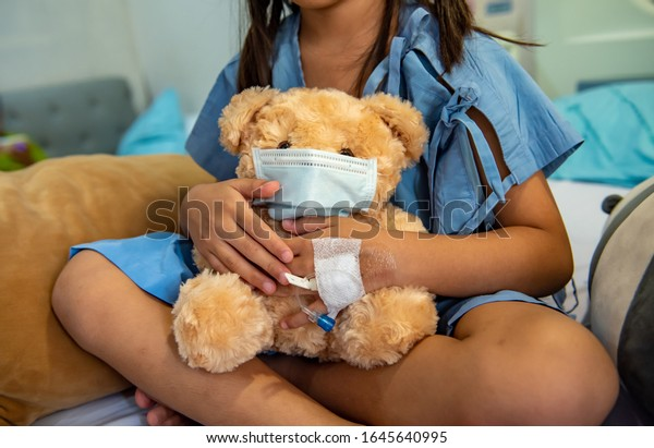 Teddy bear wearing face mask or protective mask sitting with children girl on the bed hospital. Health care and encouragement concept.
