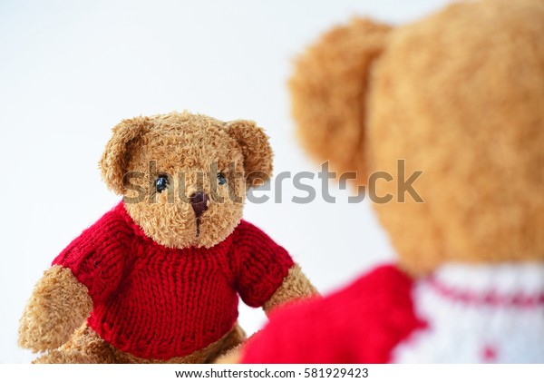 Teddy Bear wearing red knitted sweaters talking to another teddy bear. Concept about one-side love, difficult love and expectancy. Face-to-Face Conversation