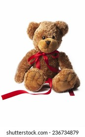 Teddy bear wearing red ribbon tied in bow around neck on white background