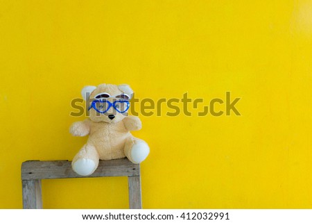8fd7b9970fd Teddy bear wearing sunglasses sitting on backrest chair isolate on yellow  background with copy space.