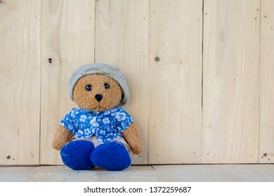 Teddy Bear wears a shirt, shorts, hat and slipper on wooden floor