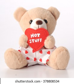 Teddy Bear with white pants and red heart shaped detail carrying Hot Stuff  heart shaped Massage