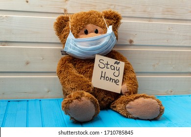 teddy bear with words stay at home in protective medical mask on the wooden background