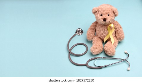 Teddy Bear yellow gold ribbon with stethoscope on blue background , Bone cancer, childhood cancer awareness,  World Suicide Prevention Day, Sarcoma Awareness