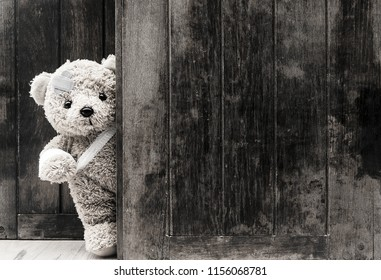Teddy bears sick with bandages and broken hand on old wood background with copy space, black and white tone.