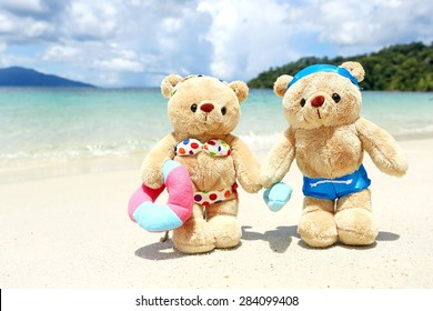 teddy bears in swimsuit and bikini walking on sand beach , background mountain and blue sky by the sea