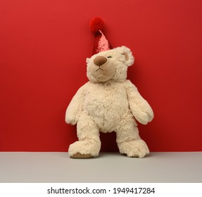 teddy beige bear in a red cap on a red background, festive background