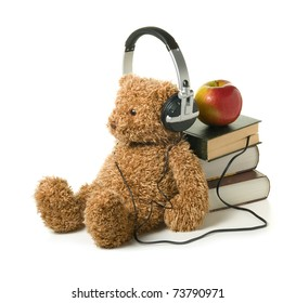 Teddybear with headphones on a white background. Concept of audiobook for children.