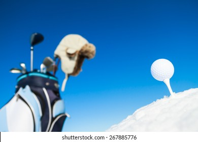 Tee, golf ball and equipment in snowy landscape.