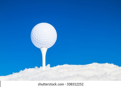 Tee, golf ball and equipment in snowy landscape
