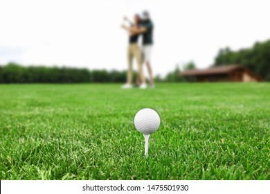 Tee with golf ball on green course