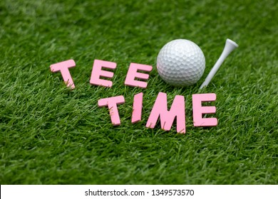 Tee Time with golf ball and tee are on green grass. It is golf invitation.