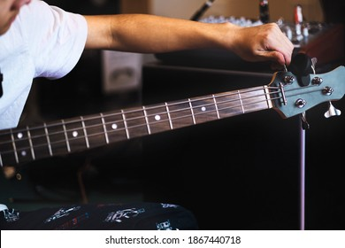 Teen adjusting and tuning guitar strings in his music studio at home. Student active life under covid-19 pandemic the new normal. Music, child art activity and tuning instrument background.