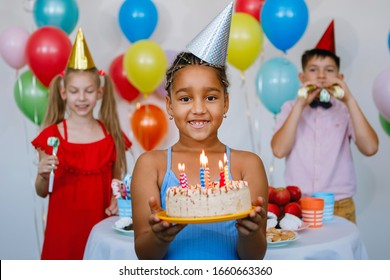 Teen african american girl in a yellow cap with a cake in her hands, smiling, celebrating a birthday, ready to blow out the candles. Selected focus on the main subject.