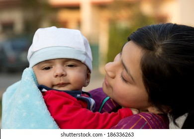 teen age girl holding her new born baby brother in lap