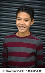 Teen Asian boy with braces smiling,  set against dark, industrial background.