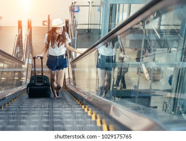 Teen Asian women standing with luggage or suitcase at the window watching aircraft taking off in the international airports in Thailand.