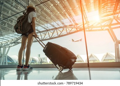 Teen Asian women standing with luggage or suitcase at the window watching aircraft taking off in the international airports in Thailand. Asian girl at International Airport.