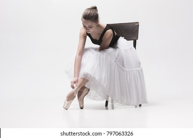 The teen ballerina in white pack sitting on chair