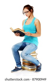 Teen beautiful girl in glasses reading a book sitting on books. Isolated on white.