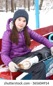 teen beautiful girl with long dark hair put on ice skate boots before skating on the ice outdoor skate rink