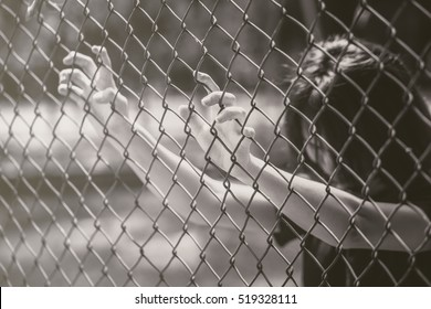 teen behide the cage or woman jailed, unhappy girl hand sad hopeless at fence prison in jail, no free and freedom struggle teen concept.