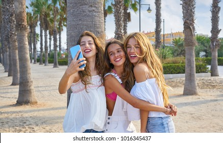 Teen best friends girls group shooting selfie photo smartphone in palm trees beach