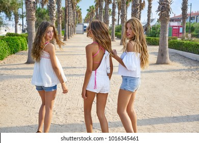 Teen best friends girls group walking happy in a palm trees beach area