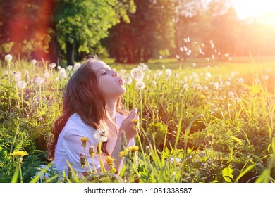 A teen blowing seeds from a dandelion flower in a spring park
