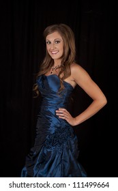A teen with a blue formal dress standing in front of a black background with a smile on her face.