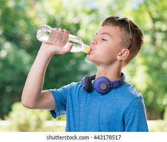 Teen boy 12-14 year old drinking fresh water from a bottle. Student teenager with headphones and sunglasses posing outdoors.