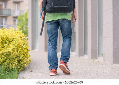 Teen boy 14 years old with backpack on the first or last school day. Excited to be back to school after vacation - outdoor back view.