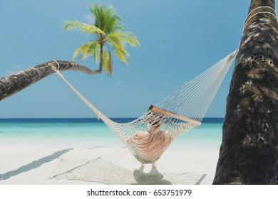 teen boy in beach hammock on the maldives