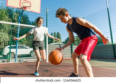 Teen boy coaching his girlfriend playing basketball, street basketball game.