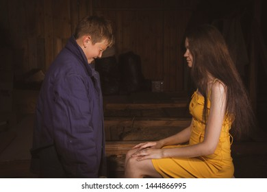 Teen boy crying near mom. Young mom girl sitting on chair in yellow dress. The child stands near his mother in blue clothes.