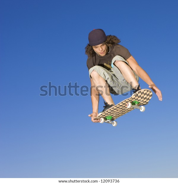 Teen boy does tricks in the half pipe at a skate park