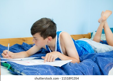 Teen boy doing homework on his bed